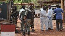 Malian anti-terrorist special forces and investigators walk at the entrance of the Kangaba tourist resort in Bamako on June 19, 2017. (HABIBOU KOUYATE/AFP/Getty Images)