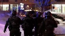 Swat team police officer walk around a mosque after a shooting in Quebec City. (Mathieu Belanger/REUTERS)