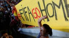 In this May 27, 2014 photo, a demonstrator shout slogans against FIFA during a protest against FIFA World Cup, at a bus station in Brasilia, Brazil. (Associated Press)