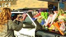 A police cruiser covered in flowers, letters and cards is shown outside the police department November 2, 2016 in Urbandale, Iowa. (Steve Pope/Getty Images)