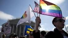 Kevin Coyne of Washington holds flags in front of the Supreme Court in Washington as the court hears arguments on gay marriage. (Carolyn Kaster/AP)