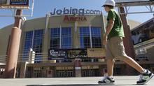 A lone pedestrian walks past Jobing.com Arena, Wednesday, June 13, 2012, in Glendale, Ariz., where the Phoenix Coyotes NHL hockey team plays home games. (Associated Press)
