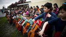 Students from grades 4 through 7, who are part of the string orchestra program, play their instruments outside Dr. Annie B. Jamieson Elementary School in Vancouver, British Columbia, Wednesday, April 16, 2014. (Rafal Gerszak for the globe and mail)