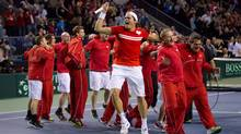 Canada's Milos Raonic, centre, of Toronto, Ont., celebrates with his teammates after defeating Italy's Andreas Seppi during the fourth set of a Davis Cup tennis quarter-final singles match in Vancouver, B.C., on Sunday April 7, 2013. The victory gave Canada the quartfer-final win over Italy. (DARRYL DYCK/THE CANADIAN PRESS)
