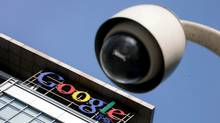 The Google logo is seen on the top of its China headquarters building behind a road surveillance camera in Beijing. (JASON LEE/JASON LEE/REUTERS)