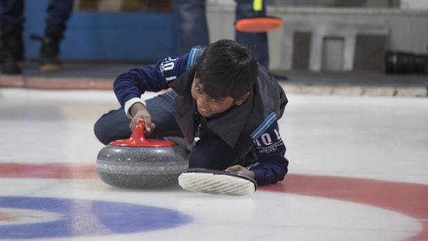 Arun Daniel, 11, a refugee from Sri Lanka, slips on the ice while attempting to throw a stone during a day trip to the Royal Canadian Curling Club, on March 15, 2017.