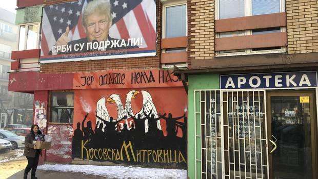 A woman walks by a billboard in the Serb-dominated northern half of Mitrovica, Kosovo hailing Donald Trump's victory.