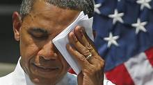 President Barack Obama wipes his face as he speaks about climate change, Tuesday, June 25, 2013, at Georgetown University in Washington. The president is proposing sweeping steps to limit heat-trapping pollution from coal-fired power plants and to boost renewable energy production on federal property, resorting to his executive powers to tackle climate change and sidestepping the partisan gridlock in Congress. (Charles Dharapak/AP)
