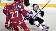 Latvia's Ronalds Kenins, right, attempts to evade Russia's Alexei Tereshenko and Fyodor Tyutin, back, during the 2013 Ice Hockey IIHF World Championships Group B match Russia vs Latvia in Helsinki, Finland, Saturday, May 4, 2013. (Martti Kainulainen/THE CANADIAN PRESS)