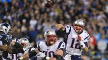 New England Patriots quarterback Tom Brady (12) throws a touchdown pass to tight end Rob Gronkowski (87) (not pictured) as guard Logan Mankins (70) blocks and Carolina Panthers defensive tackle Kawann Short (99) defends in the third quarter. (USA TODAY Sports)