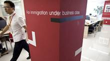 In this Aug. 1, 2011 photo, a worker walks inside an office of Beijing Goldlink Go-Abroad Consulting Co., an immigration consulting firm assisting Chinese to immigrate to Canada and the United States. (Alexander F. Yuan/AP)