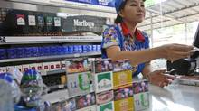 A shop attendant gives change to a customer as cigarettes packages are displayed behind the counter at a convenience store in Jakarta, Indonesia, Tuesday, June 24, 2014. (Tatan Syuflana/AP)
