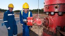 The Quest Project will be transporting CO2 from the Scotford Upgrader, near Edmonton, Alberta in Canada, through an 80 kilometer underground pipeline to between three to eight injection wells. Photo shows Shell employees standing next to the wellhead of the first Quest CO2 injection well. (Shell)