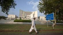 A man walks past the Supreme Court building in Islamabad on July 12, 2012. (FAISAL MAHMOOD/REUTERS)