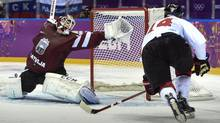 Latvia goaltender Kristers Gudlevskis reaches for a shot from Canada's Chris Kunitz during first period quarter-final hockey action at the Sochi Winter Olympics Wednesday, February 19, 2014 in Sochi. (Paul Chiasson/THE CANADIAN PRESS)
