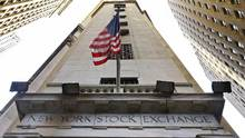 In this Friday, Nov. 13, 2015, file photo, the American flag flies above the Wall Street entrance to the New York Stock Exchange. (Richard Drew/AP)