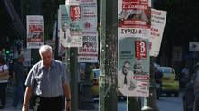 Pedestrians walk past pre-election posters in Athens on June 13, 2012. Greece holds general parliamentary elections on June 17. (PASCAL ROSSIGNOL/REUTERS)