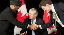 Prime Minister Stephen Harper looks on as Dr. Andrew Bennett (right), shakes hands with Muslim cleric Lai Khan Malik after naming Mr. Bennett ambassador to the Office of Religious Freedom in Maple, Ont., Feb.19, 2013. (Frank Gunn/THE CANADIAN PRESS)