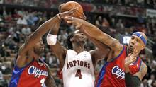 Toronto Raptors forward Chris Bosh has a shot blocked by Los Angeles Clippers defenders Rasual Butler, left, and Drew Gooden in Toronto on Wednesday. (MIKE CASSESE/Mike Cassese/Reuters)