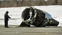 A Transportation Safety Board investigator inspects an engine at the crash site of Air Canada AC624 on March 30, 2015, at Stanfield International Airport in Halifax. The flight , which was carrying 133 passengers and five crew members, crashed the day before during a snowstorm. (Andrew Vaughan/THE CANADIAN PRESS)