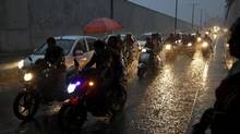 In this photo, commuters on their vehicles move through an underpass during a heavy rain shower in Ahmedabad, India, Sept. 18, 2015. Rains were 16 percent below average so far over the four-month monsoon season that ends this month due to an El Nino weather pattern, which can lead to scorching weather across Asia and east Africa but heavy rains and floods in South America. A University of Victoria professor is warning El Nino may hit Canada's West Coast this year. (AMIT DAVE/REUTERS)