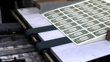 Sheets of U.S. one dollar bills roll off the press at the Bureau of Printing and Engraving in Washington. (Hillery Smith Garrison/AP)