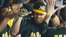 Oakland Athletics Josh Reddick (C) is congratulated by team mates in the dugout after he hit a home run against the Toronto Blue Jays, his third of the game, in the sixth inning of their American League MLB baseball game in Toronto August 9, 2013. (FRED THORNHILL/REUTERS)