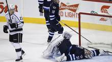 Winnipeg Jets' goaltender Ondrej Pavelec lies on the ice after a after Justin Williams shot beat him during third period NHL action in Winnipeg on Friday, October 4, 2013. (JOHN WOODS/THE CANADIAN PRESS)