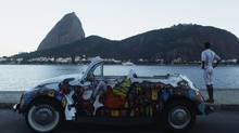 Art collector Andrei de Lima poses next to his 1972 Volkswagen Beetle decorated with graffiti depicting a hillside favela, as he looks at Sugarloaf mountain in the background, in Rio de Janeiro, March 12, 2013. A fragile economic recovery, expiring tax breaks and tighter credit have cooled Brazil's demand for new cars after a consumer boom that doubled sales in five years. (PILAR OLIVARES/REUTERS)