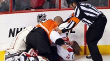 Linesman Francois St. Laurent tries to pull Philadelphia Flyers goalie Ray Emery off of Washington Capitals goalie Braden Holtby (Associated Press)