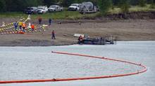 Crews prepare a boom on the Gleniffer reservoir to stop oil from a pipeline leak near Sundre, Alta., on June 8, 2012. Plains Midstream Canada says one of their non-functioning pipelines leaked between 1,000-3,000 barrels of oil. (Jeff McIntosh/The Canadian Press)