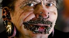 German Rolf Buchholz shows his face with 168 piercings as he visits the 20th Tattoo Convention in Berlin. A Dubai nightclub that hoped to feature Buchholz, who holds the world record for having the most piercings, said in an emailed statement Sunday, Aug. 17, 2014, that he was refused entry to the Gulf city because of security concerns. The German man now has 453 piercings, including many in his face and genitals, according to Guinness World Records. (Markus Schreiber, File/AP Photo)