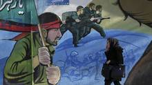 An Iranian woman walks past a mural depicting Iranian armed forces in the battlefield, at Palestine Sq. in Tehran, Iran, Saturday, Jan. 16, 2016. The end of Western sanctions against Iran loomed Saturday as Iran's foreign minister suggested the U.N. atomic agency is close to certifying that his country has met all commitments under its landmark nuclear deal with six world powers. (Vahid Salemi/AP)