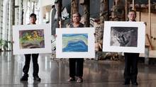 Survivors of Alberni Indian Residential School, left to right, Chuck August, Gina Laing,and Dennis Thomas of Port Alberni hold up their paintings at The Canadian History Museum June 1, 2015 in Gatineau, Quebec. (DAVE CHAN FOR THE GLOBE AND MAIL)