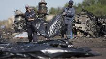 Ukrainian Emergency workers carry a victim's body in a bag at the crash site of Malaysia Airlines Flight 17 near the village of Hrabove, Donetsk region, eastern Ukraine, Monday, July 21, 2014. (Dmitry Lovetsky/AP)