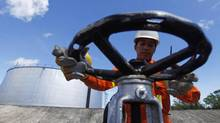 A worker opens a gauge near crude oil tanks on Bunyu island, Indonesia's East Kalimantan province in this February 8, 2011 file photograph. (BEAWIHARTA/REUTERS)