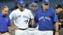 Toronto Blue Jays starting pitcher Brandon Morrow (C) leaves the game with an injury beside manager John Farrell (R) during the first inning of their interleague baseball game against the Washington Nationals in Toronto June 11, 2012. (MIKE CASSESE/REUTERS)