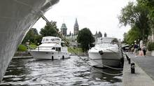 A boat heads south along the Rideau Canal in downtown Ottawa on Tuesday, July 29, 2008. (Sean Kilpatrick/The Canadian Press)