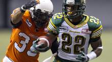 B.C. Lions' Andrew Harris, left, tries to tackle Edmonton Eskimos Joe Burnett during the first half of a CFL game in Vancouver, B.C., on Friday, July 20, 2012. (JONATHAN HAYWARD/THE CANADIAN PRESS)