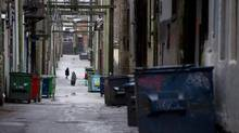 People walk through a back alley in Vancouver's Downtown Eastside. (JONATHAN HAYWARD/THE CANADIAN PRESS)
