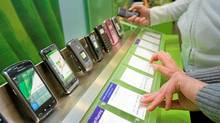 Customers browse the phones at the Telus store in Toronto's Eaton's Centre. (JENNIFER ROBERTS FOR THE GLOBE AND MAIL)