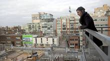Condo owner Eva Kanovich looks onto a neighbouring condo under construction from her balcony in downtown Toronto on Feb. 4, 2012. (Pawel Dwulit/The Canadian Press/Pawel Dwulit/The Canadian Press)