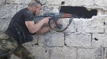 A Free Syrian Army fighter aims his weapon as he takes a defensive position in Qaboun area in Damascus on June 20, 2013. (REUTERS)