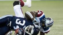 Toronto Argonauts running back Jerious Norwood (34) gets tackled by Montreal Alouettes line backer Kyries Hebert, right, during first half CFL football action in Toronto, on Friday, Nov. 1, 2013. (NATHAN DENETTE/THE CANADIAN PRESS)
