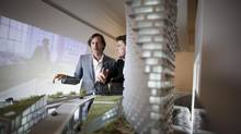 Architect Bjarke Ingels, right, and Ian Gillespie, left, look over a model of the 52-storey building project in Vancouver. (Rafal Gerszak for the globe and mail)