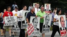"""Protesters holding """"Arthur T"""" signs picket outside a Market Basket Supermarket job fair in Andover, Mass., Monday, Aug. 4, 2014. (Elise Amendola/The Associated Press)"""
