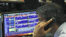 A broker speaks on the phone in a trading room of a Portuguese bank in this photo from March. The Bank of Canada says the European financial situation was a key 'foreign headwind' behind the Bank's decision to keep its interest rate at 1 per cent. (FRANCISCO SECO/ASSOCIATED PRESS)