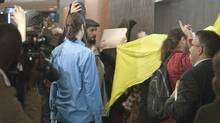 Family and friends of four youths charged in the metro smoke bombing incidents shield themselves from the cameras as the bail hearing was postponed at the courthouse Monday, May 14, 2012 in Montreal. (Ryan Remiorz/THE CANADIAN PRESS)