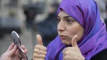 Nariman Eldoraini gives a thumbs up as she checks her Niqab in a mirror during a gathering in Montreal on Jan. 12, 2014, to oppose the proposed Charter of Quebec Values. (GRAHAM HUGHES/THE CANADIAN PRESS)