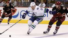 Vancouver Canucks left wing Raffi Torres shields Phoenix Coyotes defenseman Keith Yandle from the puck in the third period during an NHL game in Glendale, Arizona, March 8, 2011. (RICK SCUTERI/REUTERS)